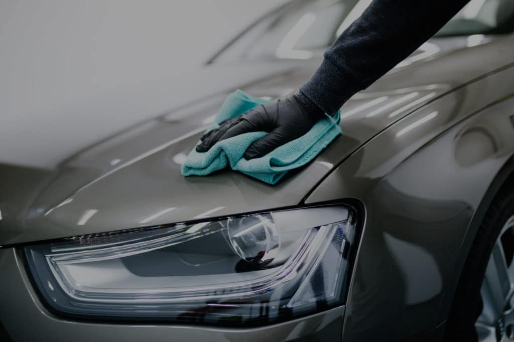 Our experienced detailer cleaning car with microfiber cloth